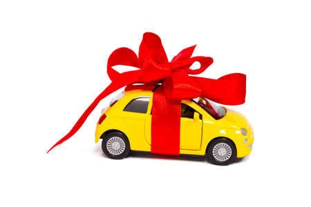 A gift  A comfortable car with a red bow isolated on white background photo