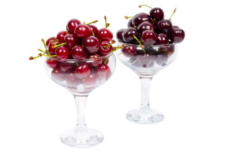 Two cups of ripe cherry and sweet cherry isolated over white background photo