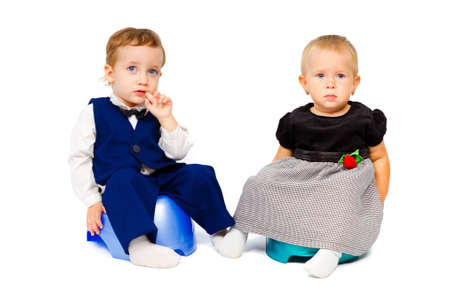 Trendy kids are sitting on the pot isolated on white background photo