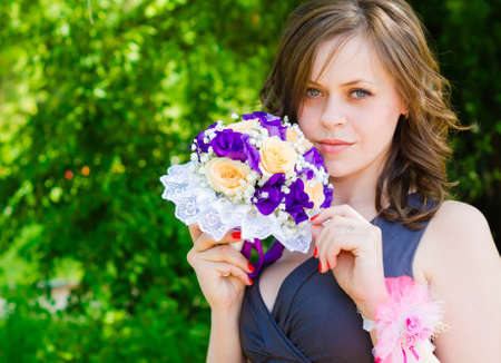 A pretty girl with a bouquet of the bride on the background of green leaves