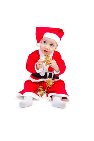 Adorable baby in the costume of Santa Claus is sitting on the floor isolated on white background