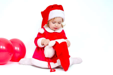 Beautiful girl looking for Christmas gifts in the Christmas sock on white background photo