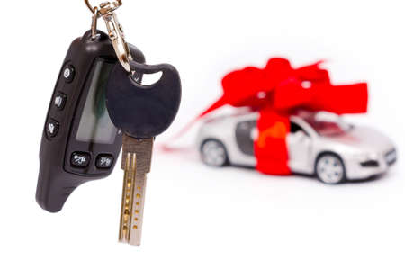 Car keys on the background of the machine with a red bow isolated on white background. Gift