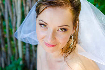 Charming bride with beautiful wedding makeup and with stylish hairstyle closeup