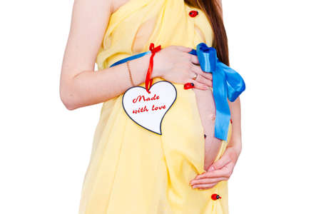 nacimiento bebe: Primer plano del vientre de la mujer embarazada en el tejido de color amarillo con un lazo azul en el fondo blanco. Coraz�n con etiqueta Hecho con amor