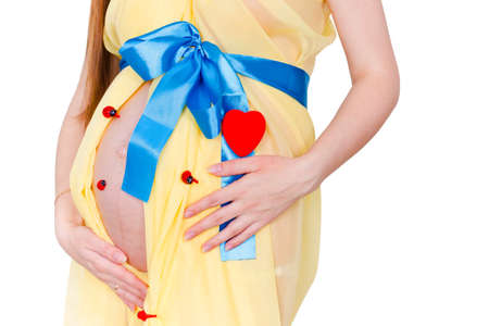 lovely pregnant woman: Close up belly of pregnant woman in the yellow fabric with a blue bow near the heart and ladybirds at white background Stock Photo