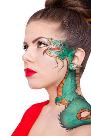 Closeup of the girls face with a green dragon tattoo isolated on white background