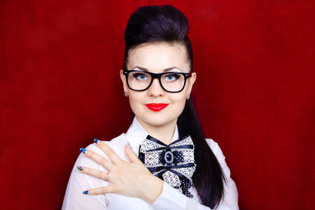 Cute model with decorative make up and beautiful hairstyle on red background photo