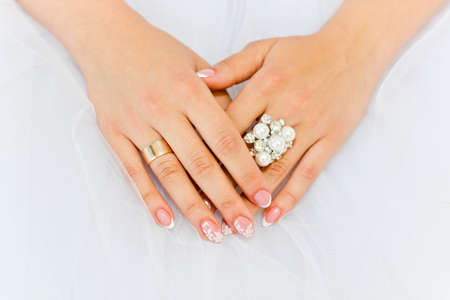 Gemstone ring with pearls on the fingers of the bride on background of wedding dress photo