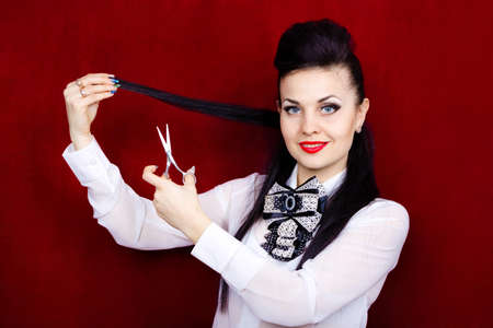 Girl hairdresser is cutting her hair with scissors