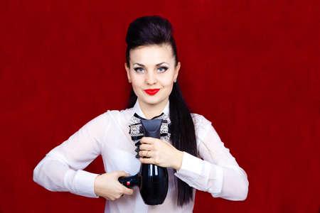Girl hairdresser makes hair styling using a hair dryer