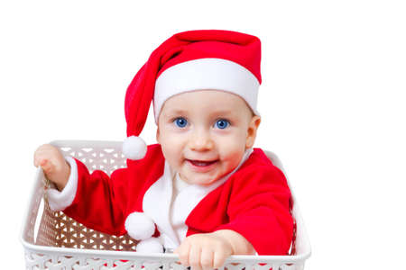 Happy child in the costume of Santa Claus sitting in a box isolated on white background. The child is one year.