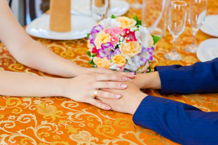 Male and female hands holding each other at a table in the restaurant photo