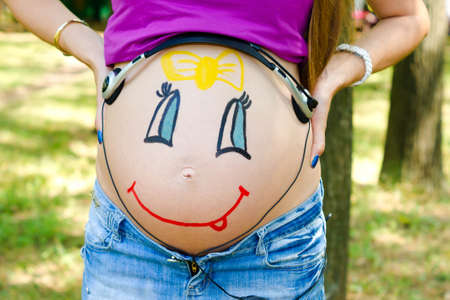 life giving birth: On the abdomen of a pregnant woman painted smiling face of her unborn daughter Stock Photo
