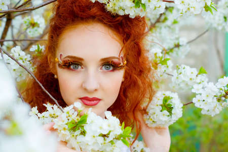 Portrait of beautiful woman with clean skin looking through spring cherry flowers