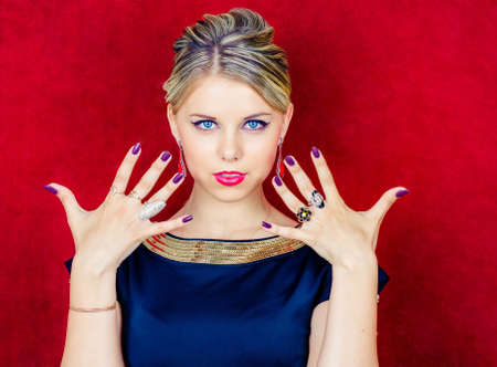 Portrait of young beautiful woman in jewelry with perfect makeup on red background