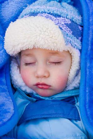 Pretty baby sleeps in a stroller on a walk in the fresh air photo