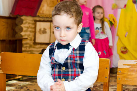 Sad boy in a vest and bow tie seated on a chair at the party in the kindergarten