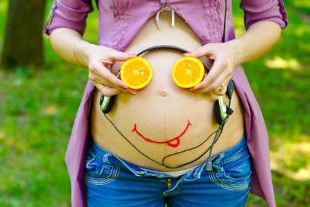 life giving birth: En el vientre de una mujer sonriente cara del beb� embarazada y auriculares. El ni�o escucha la m�sica en el �tero Foto de archivo