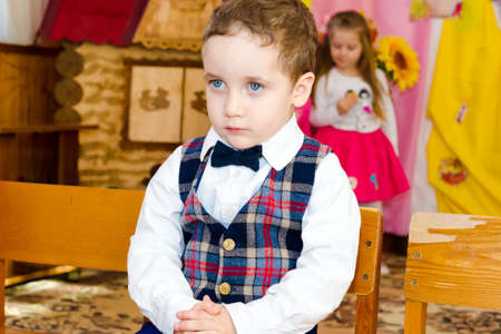 The little gentleman in a shirt with a vest and bow tie seated on a chair in kindergarten