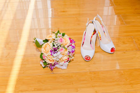 Wedding bouquet and fashionable shoes bridesmaid lie on laminated parquet on the floor