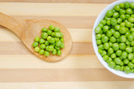 Wooden spoon and bowl with seeds of green peas on the kitchen table Reklamní fotografie