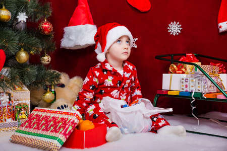 A beautiful baby in a santa hat sits near a Christmas tree