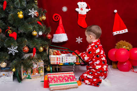 A beautiful baby puts Christmas presents on a sleigh