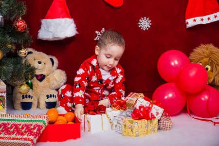 A beautiful boy in pajamas unpacks Christmas presents