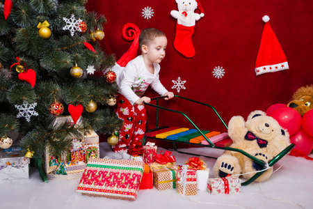 A charming boy rolls a sleigh next to a lot of presents near a Christmas tree