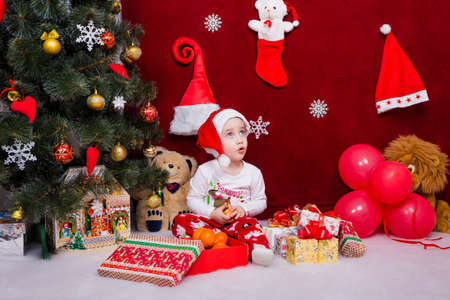 A charming child was surprised to receive a large number of Christmas presents Reklamní fotografie