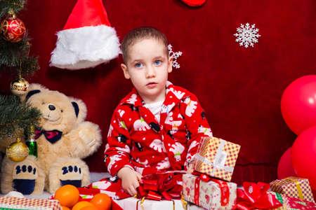Ð¡ute baby in pajamas parses Christmas presents Close up