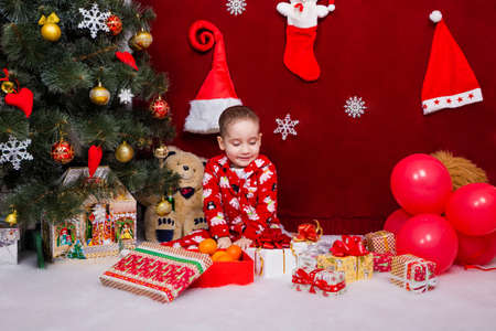 A cute baby in pajamas was delighted with Christmas presents under the tree Stock Photo