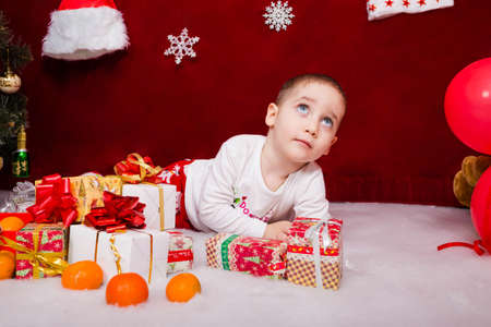 A cute kid lies with presents next to a Christmas tree Reklamní fotografie