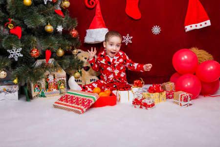A nice baby in pajamas was delighted with a lot of Christmas presents near the Christmas tree