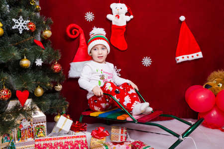 A nice boy sits next to a Christmas tree Reklamní fotografie
