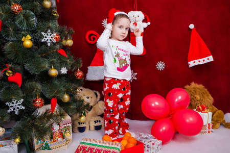 A sad kid is standing by a Christmas tree