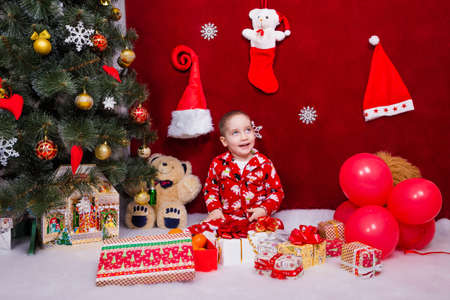 A smiling child sits with a lot of presents next to a Christmas tree