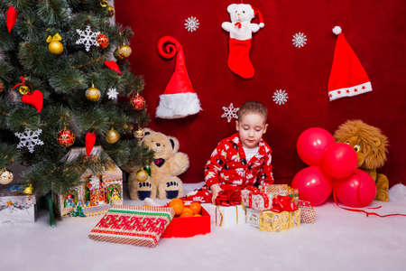 A wonderful baby in pajamas looks at Christmas presents under the tree Reklamní fotografie