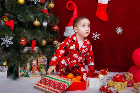 Charming baby in pajamas looking for Christmas gifts under the Christmas tree