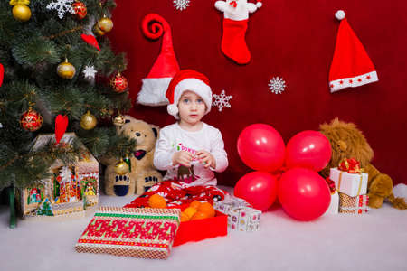 Charming baby sitting by the Christmas tree Reklamní fotografie
