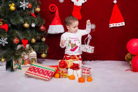 Charming boy unpacks Christmas presents Reklamní fotografie