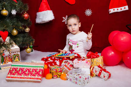 Charming little kid plays with toys found under the Christmas tree Reklamní fotografie