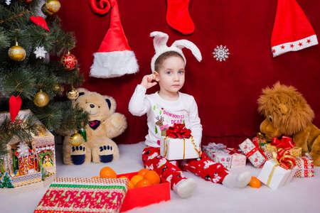 Cute little boy is sitting with a gift near a Christmas tree Reklamní fotografie
