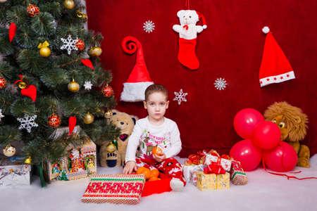 Cute little boy was upset when he found tasty mandarins under the Christmas tree Reklamní fotografie