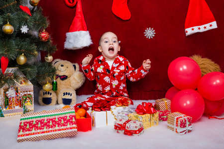 Funny child was delighted with the number of Christmas gifts under the Christmas tree