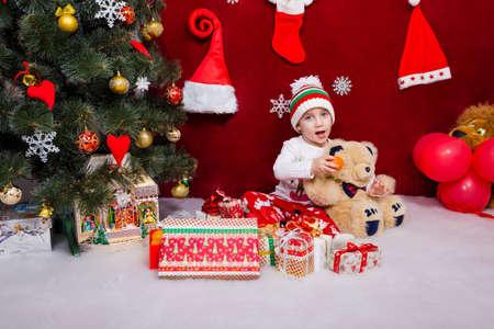 Funny kid feeds tangerines teddy bear next to Christmas tree