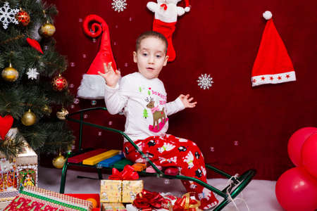 Funny kid sits on a sleigh next to a Christmas tree and watches soap bubbles