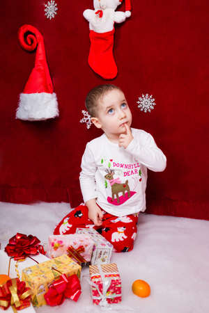 The cute kid thought about the gift that Santa Claus would bring him