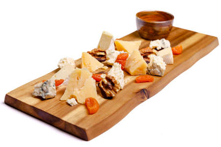 Close-up view of delicious cheese plate with nuts on wooden tabletop. Isolate on a white background